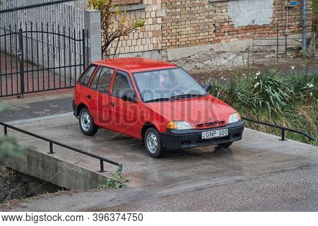 BUDAPEST, HUNGARY - CIRCA 2019: Old Suzuki Swift parked on a driveway, rainy weather. Popular small car made in the beginning of 90s. September 1992 production in Esztergom, Hungary started