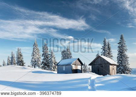 Fantastic winter landscape with wooden house in snowy mountains. Christmas holiday concept