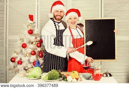 Menu For Our Family. Man And Woman Chef Santa Hat Near Christmas Tree Hold Blackboard Copy Space. Co