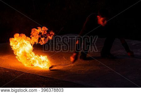 Fascinating And Dangerous. Man Manipulate With Burning Poi In Dark. Burning Fuel And Energy. Sparks