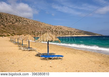 Sun Beds And Umbrellas At Agia Theodoti Beach On Ios Island. A Wonderful Beach With The Golden Sand