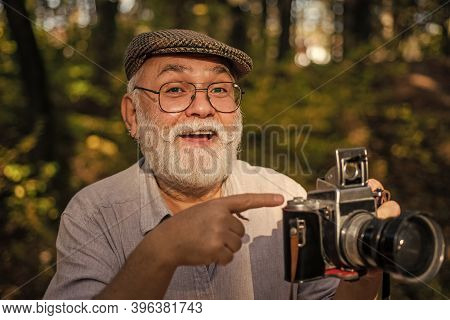 Look At This. Old Photographer Pointing At Retro Camera. Bearded Man Pointing Finger Outdoors. Point