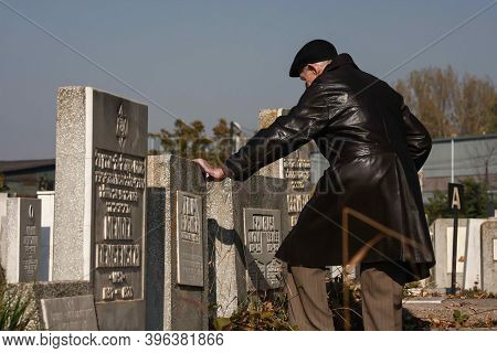 Bucharest, Romania - October 29, 2008: A Senior Man Touches A Grave From A Jewish Cemetery In Buchar