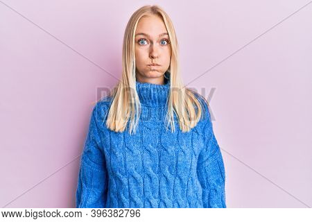 Young blonde girl wearing wool winter sweater puffing cheeks with funny face. mouth inflated with air, crazy expression.