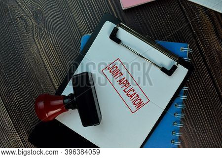 Red Handle Rubber Stamper And Joint Application Text Isolated On The Table.