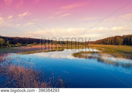 Magical Sunrise Over The Lake With A Beautiful Reflection On The Water. Serene Lake In The Early Mor