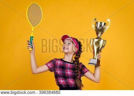 Winner Child With Racquet And Champions Cup. Teen Girl Win Tennis Championship. Sport. Tennis Or Bad