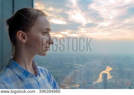 Portrait Of Pensive Woman Looking At Cityscape Through Window Of Skyscraper. Summer Time, Cloudy, Da