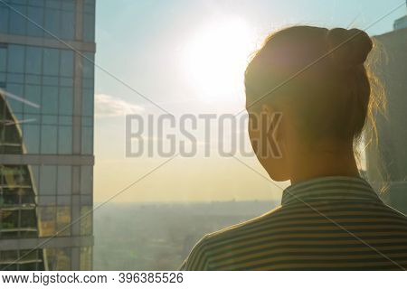 Back View Of Woman Silhouette Looking At Cityscape Through Window Of Skyscraper. Summer Time, Sunset