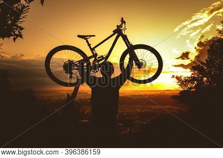 Silhouette Of A Mountain Biker Holding A Bicycle Over His Head At Sunset. Mtb, Enduro, Freeride Back