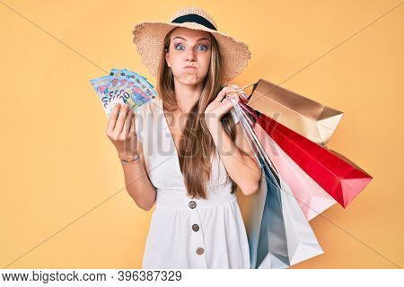 Young blonde girl holding shopping bags and euro banknotes puffing cheeks with funny face. mouth inflated with air, catching air.