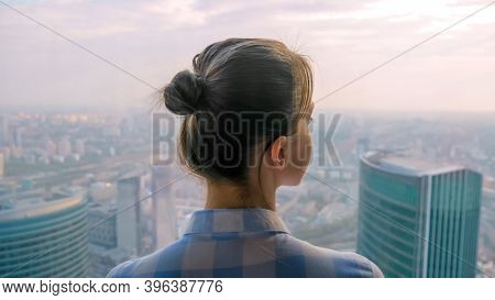Back View Of Woman Looking At Cityscape Through Window Of Skyscraper. Summer Time, Cloudy, Daylight.