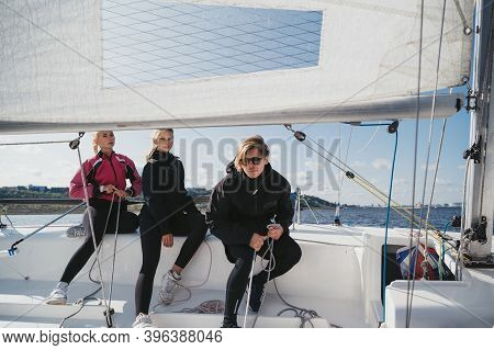 A Young Guy And Two Pretty Girls Set Off From The Pier On A White Sailing Yacht For A Weekend Trip O