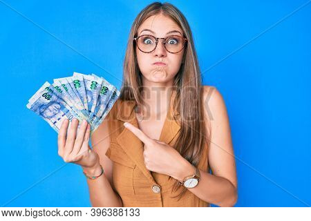 Young blonde girl holding south african rand banknotes puffing cheeks with funny face. mouth inflated with air, catching air.