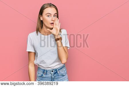 Beautiful young blonde woman wearing casual white t shirt hand on mouth telling secret rumor, whispering malicious talk conversation