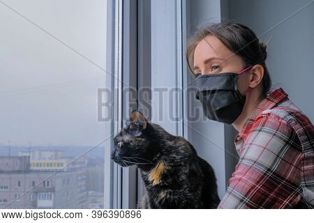 Portrait Of Pensive Woman In Black Medical Face Mask And Black Cat Looking Out Of Window In Grey Roo