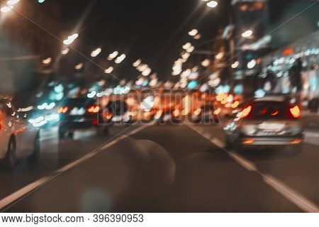 Fast Driving Traffic At Night. Abstract Blurred Background Of Urban Moving Cars With Bright Brake Li