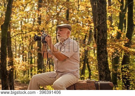 Every Man Has His Hobby. Elderly Man Look At Camera In Autumn Nature. Doing Photography As Hobby. La