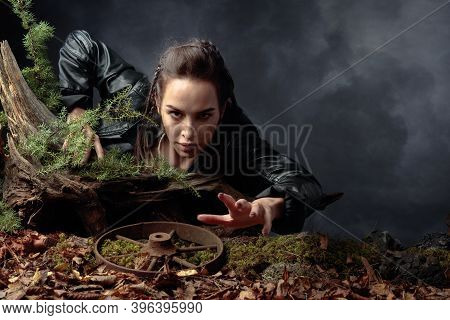 A Young Woman In A Black Leather Jacket Climbs Out Of The Pit Holding On To A Snag. Angry Girl Stret