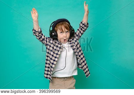 Cute Boy 4-5 Years Old In A Baseball Cap Listening To Music With Headphones On An Isolated Green Bac