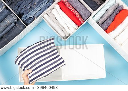 Female Hands Folding And Puting Clothes To Baskets. Vertical Storage Of Clothing, Tidying Up, Room C