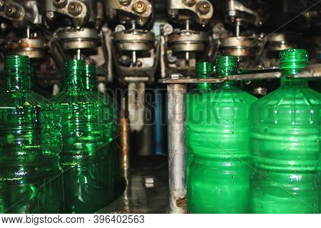 Green Plastic Bottles In The Conveyer. The Concept Of Producing Clean Water And Beverages