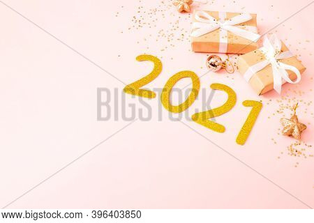 Top View Of Gift Box And Golden Stars Confetti And Numbers 2021 On Pink Pastel Background. Festive N