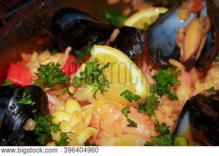 Closeup Of Seafood Paella With Lemons, Mussels, And Rice