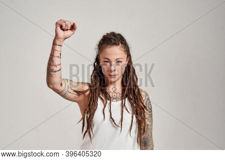Portrait Of Young Tattooed Caucasian Woman With Dreadlocks Wearing White Shirt, Looking Confident At