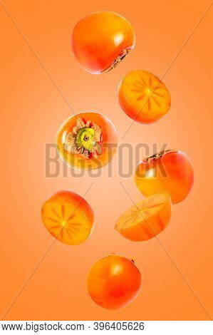 Khaki Fruits Isolated In The Air On Orange Background