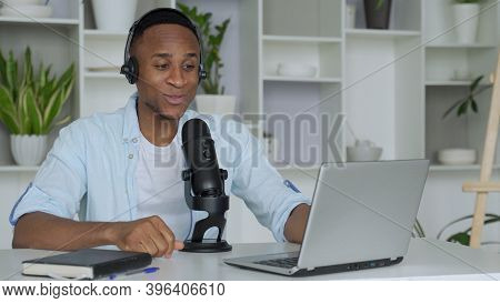 Podcast Concept - Happy Young Black Man Audio Blogger In Headphones With Laptop Computer And Microph