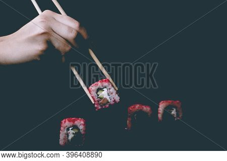 Female Hand Takes Chopsticks California Sushi Rolls With Chinese Chopsticks. Selective Focus, Black