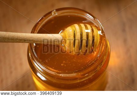 A Glass Jar Of Fragrant Honey And A Wooden Honey Dipper On A Wooden Background, Close-up