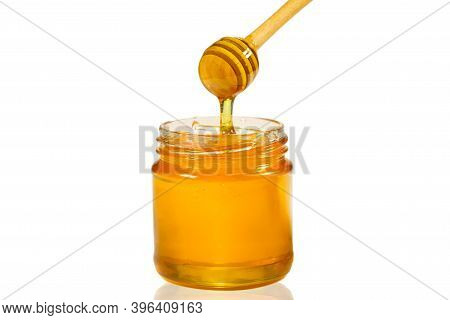 Honey Dripping From Honey Dipper Into Glass Jar Isolated On White. Close-up. Healthy Organic Thick H