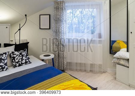 Part Of A Small Cozy Newly Furnished Bedroom In The Attic Of An Old House. Predominantly White And B