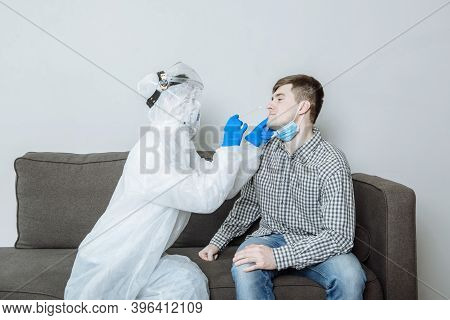 Test For Covid-19. A Doctor In A Ppe Protective Suit, Gloves And A Mask Takes A Swab With A Cotton S