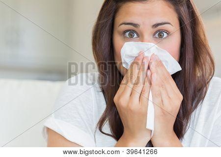 Brunette sneezing into tissue