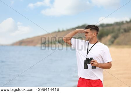 Handsome Male Lifeguard With Binocular Near Sea
