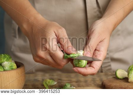 Woman Peeling Brussels Sprout At Table, Closeup