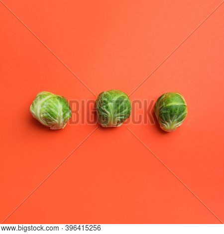 Fresh Brussels Sprouts On Coral Background, Flat Lay