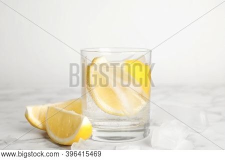 Soda Water With Lemon Slices And Ice Cubes On White Marble Table