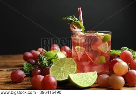 Soda Water With Grapes, Ice, Lime And Mint On Wooden Table. Refreshing Drink