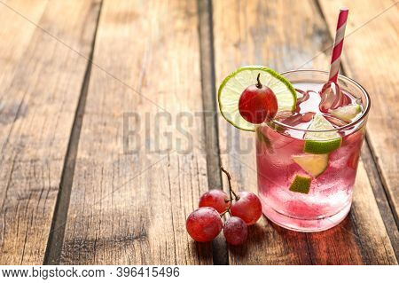 Soda Water With Grapes, Ice And Lime On Wooden Table, Space For Text. Refreshing Drink