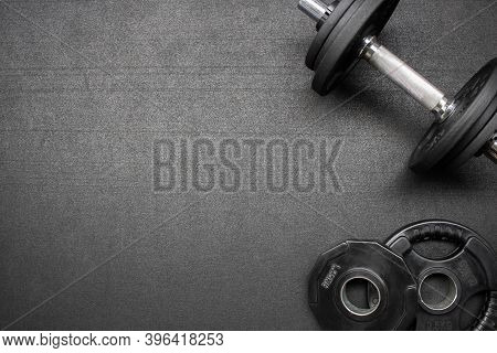 Barbell And Dumbbells On The Floor At The Gym. Top Down View Flat Lay With Bodybuilding Equipment On