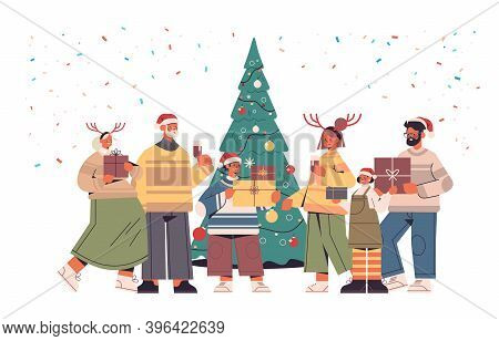 Multi Generation Family In Santa Claus Hats Holding Wrapped Gift Boxes Happy New Year And Merry Chri