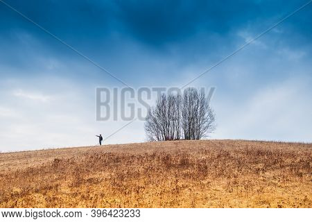 A Lonely Man Stands On A Mountain, And There Is A Lonely Tree Nearby. Large Cloudy Skies And Thick Y