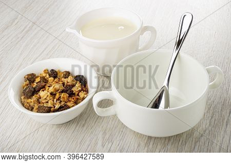 White Bowl With Baked Muesli, Pitcher With Yogurt, Teaspoon In Bowl On Wooden Table