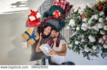 A lovely couple has wonderful time on Christmas at home together on a beautiful holiday morning. Christmas, relationship, love