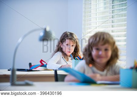 Pupil In Classroom At School. Little Pupils Busy Writing In Their Copybooks