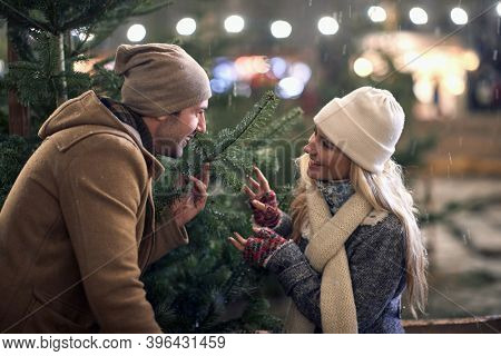 A young couple in love having good time viewing a christmas tree in a magical night on a snowy weather in the city. Christmas tree, love, relationship, Xmas, snow